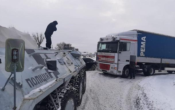 Київські поліцейські допомагають водіям долати наслідки снігопаду. Задіяні бронетранспортери, автомобілі і трактор.
