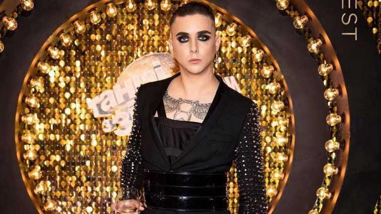 Український співак MELOVIN не припиняє дивувати фанів. Артист відвідав світський захід в екстравагантному образі, поставши у чорній сукні та жакеті з шипами.