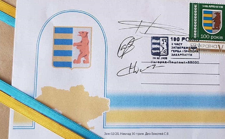 Це: герб – із синьо-жовтими смужками і ведмедем та синьо-жовтий прапор.